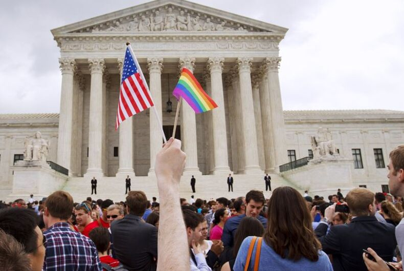 A man holds a U.S. and a rainbow flag outside the Supreme Court in Washington on June 26 after the court legalized same-sex marriage nationwide in 2015.
