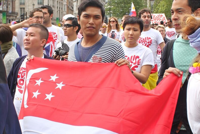 People holding up the Singaporean flag and marching with it