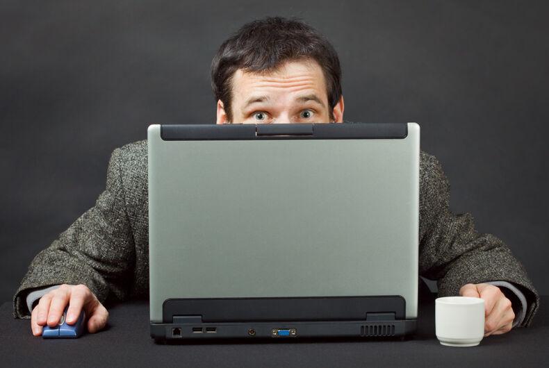 Man hiding behind laptop