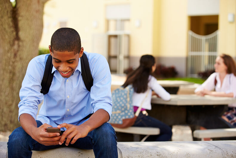 Male high school student using phone on school campus