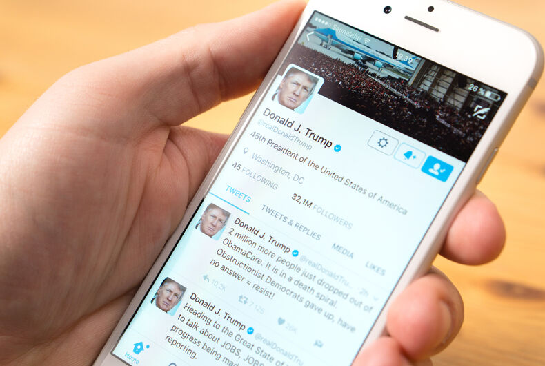 Phone in hand with the official Twitter account of Donald Trump on screen.