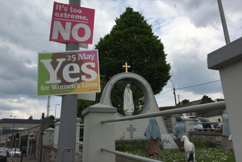 Two signs hang on a lamppost before a Christian statue. One says