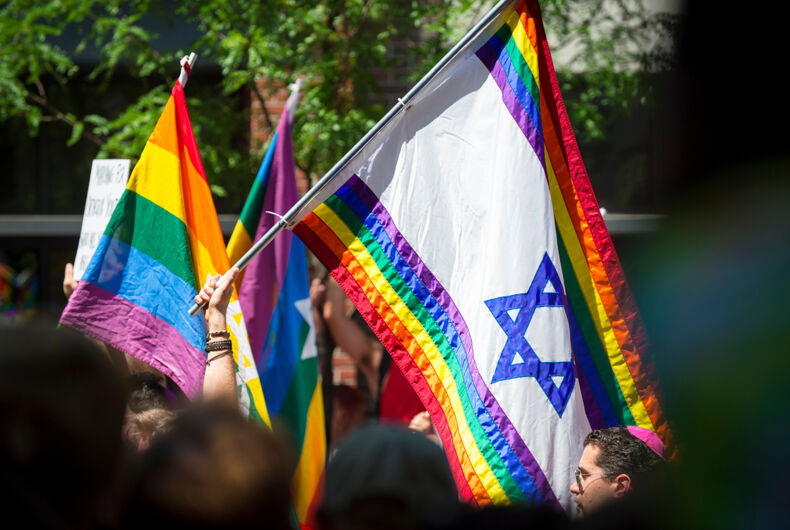 JUNE 25, 2017: Jewish participants wave Israeli Star of David rainbow flags as the Gay Pride Parade passes through Greenwich Village.
