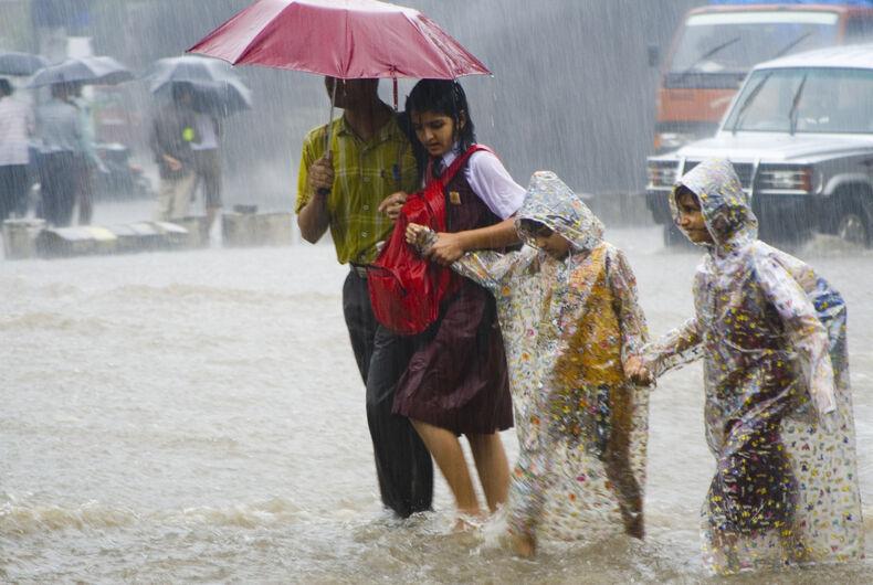 Three children go to school with their parent in monsoon rain in Mumbai, India.