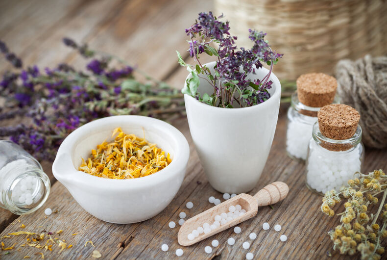 Mortar and bowl of dried healing herbs and bottles of homeopathic globules.