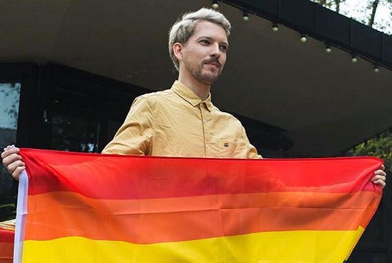 FIlmmaker Romas Zabarauskas holds a rainbow flag