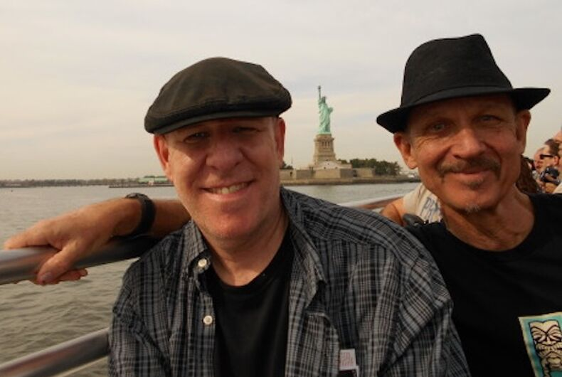 Two men on a boat with the Statue of Liberty in the background
