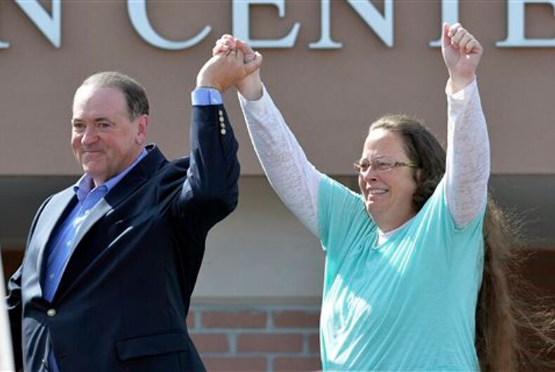 FILE - In this Sept. 8, 2015, file photo, Rowan County Clerk Kim Davis, with Republican presidential candidate Mike Huckabee at her side, greets the crowd after being released from the Carter County Detention Center, in Grayson, Ky. Davis, hauled to jail for defying a series of federal court orders and refusing to issue marriage licenses to same-sex couples, filed a 40-page court document Thursday, Sept. 24, blaming Kentucky governor Steve Beshear for all her legal woes.