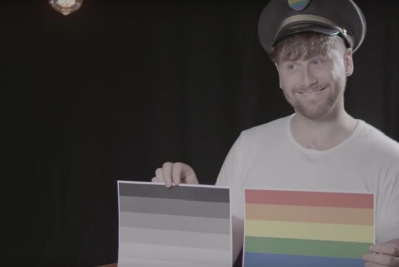 A man holding a paper copy of the rainbow flag and a paper copy of the grayscale