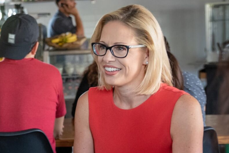 Kyrsten Sinema in a red blouse at a diner.