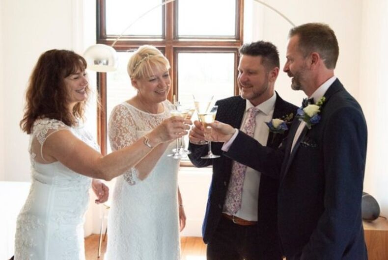 Two women in white dresses and two men in suits clink glasses