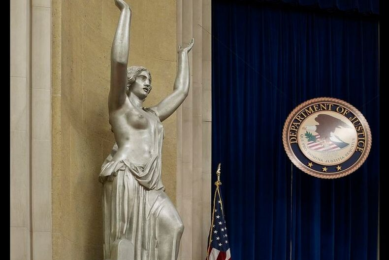 An aluminum statue of Justice showing one breast, next to the Department of Justice seal