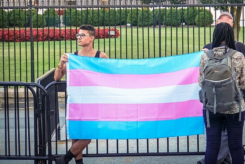 Two young people holding the blue, pink, and white transgender flag in front of the White House.