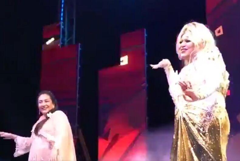 A drag queen and a woman on a stage, dancing