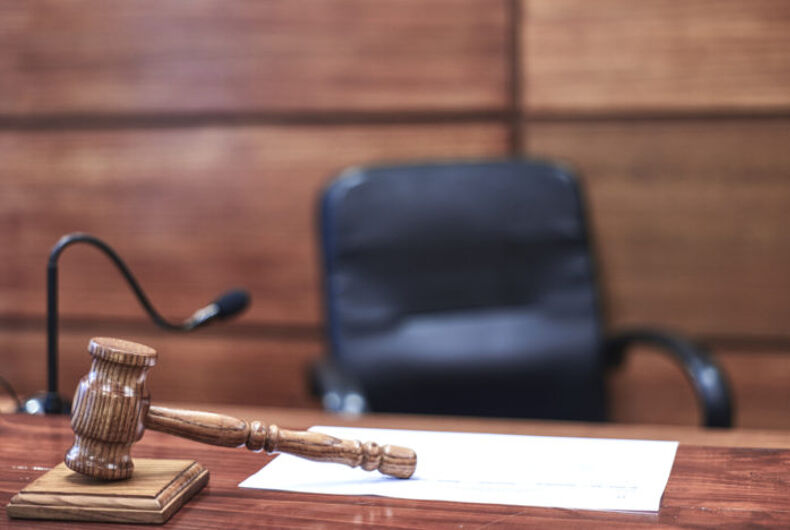 An empty chair behind a desk with a gavel and a microphone.