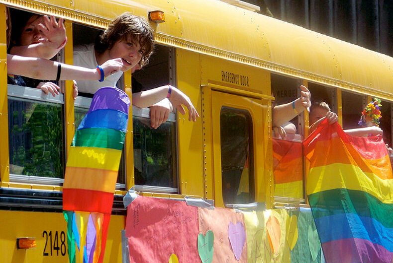A school bus with rainbow flags hanging out of it.