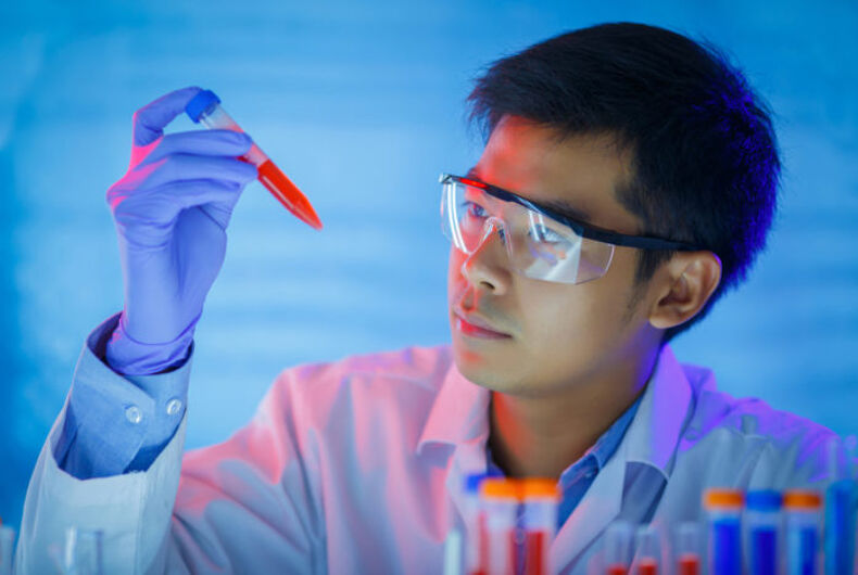 A man with gloves and lab goggles looks at a test tube with red liquid in it.