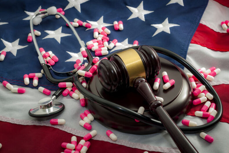 A gavel and a stethoscope and pills on top of an American flag