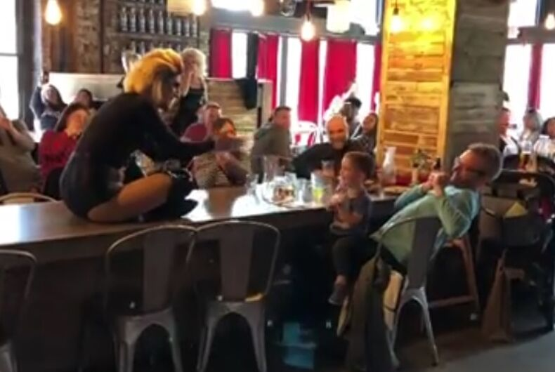 The drag queen on a table performing the song for the baby.