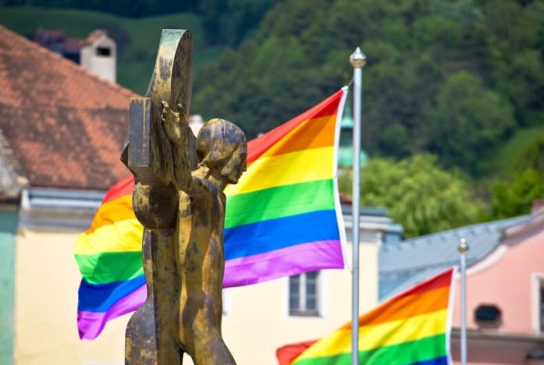 A crucifix in front of rainbow flags
