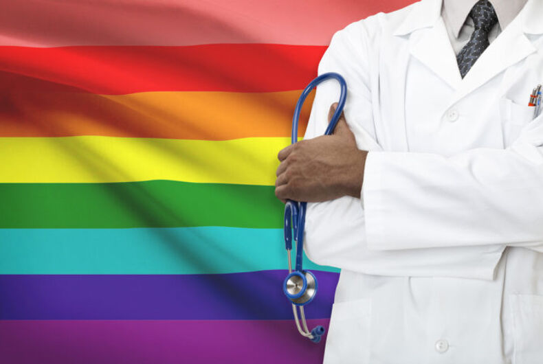 A doctor in front of the 8-striped original version of the rainbow flag.