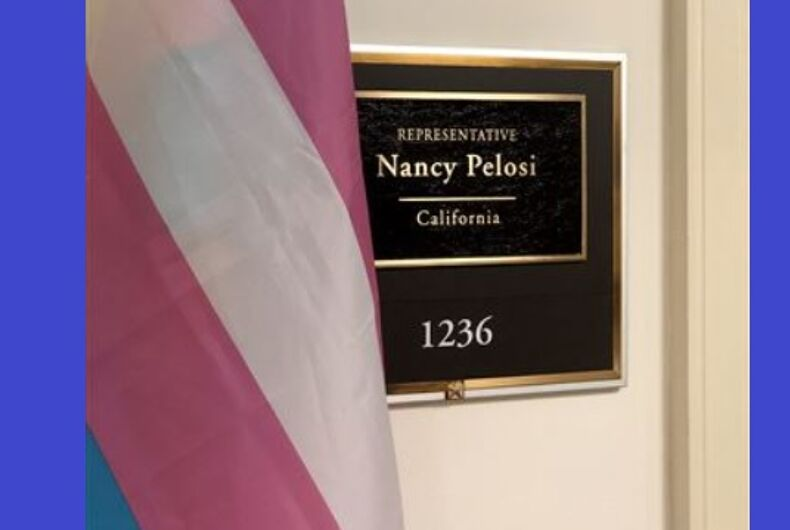 Transgender flag next to a sign for the office of Nancy Pelosi