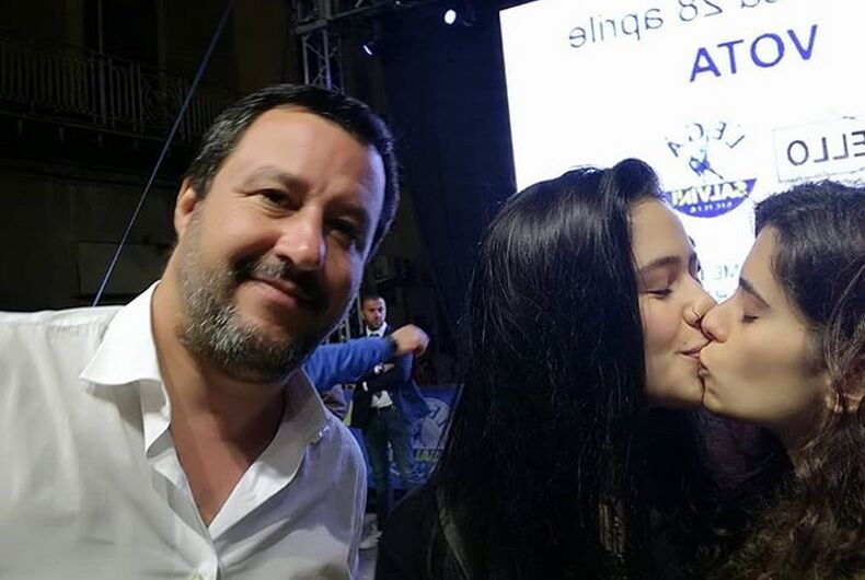 The two women kiss just next to a smiling Matteo Salvini