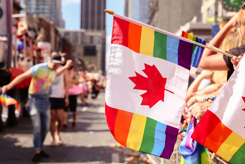 JULY 3, 2016: Crowd waves Canadian rainbow flags while watching floats at Toronto Pride parade.