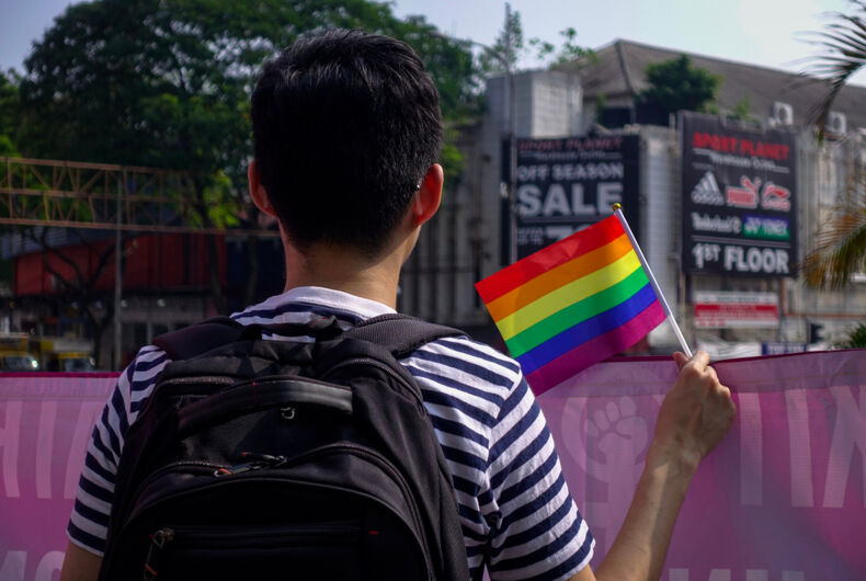 A young man quietly waves a small rainbow flag at #WomensMarchMY in conjunction with International Women's Day 2019