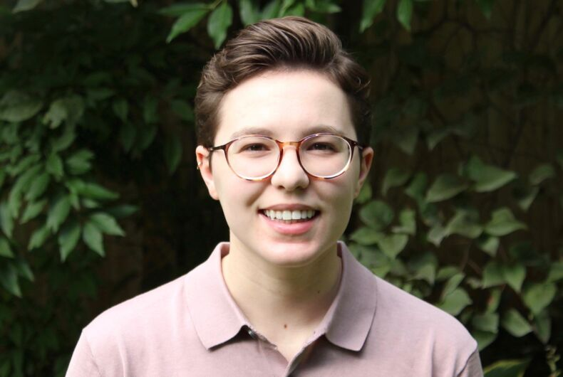 A headshot of Miranda Rosenblum, volunteer coordinator at The Trevor Project, in a beige collard shirt against a green backdrop.