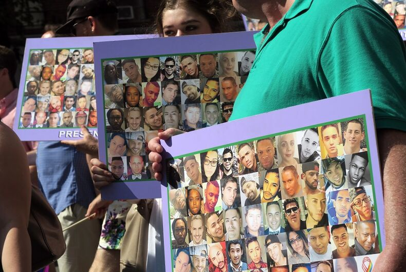 NEW YORK, NEW YORK - JULY 26, 2016: Gay Pride Parade participants holding up posters that feature images of the 49 victims of the Orlando shooting at Pulse nightclub.