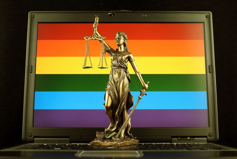 A computer with a rainbow on it and Justice, the statue, is in front of it. Perhaps it's a symbol of online, blind, queer justice, or maybe it's a satirical statement about social justice keyboard warriors. It's a stock photo, confusing in its symbolism. Also the laptop in the pic looks like it's from 1996.