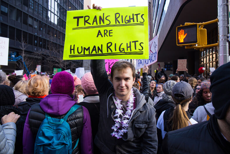 An unidentified man holds a sign that reads