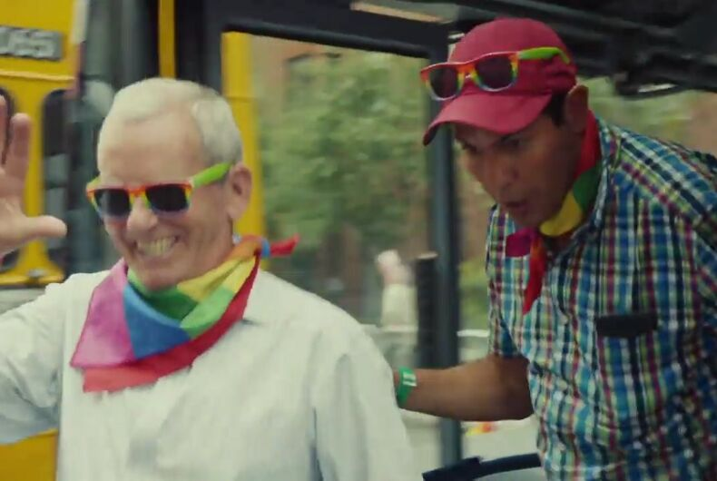 An elder and a young person step out of the bus with rainbow sunglasses and bandanas
