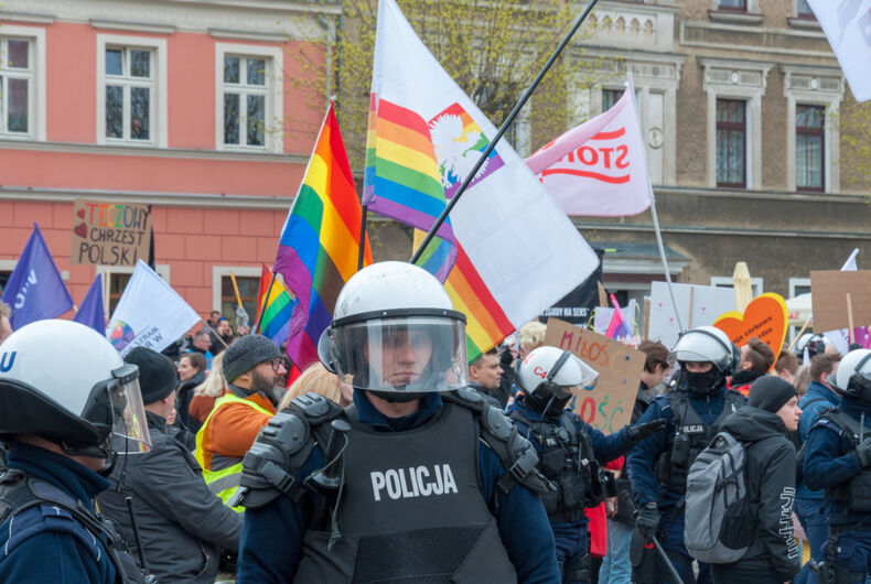 Police stand guard as LGBTQ protesters march in Gniezno, Poland.