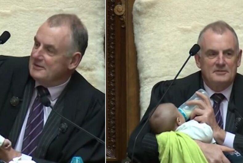 NZ Parliament Speaker Trevor Ballard holds 1-month-old Tutanekai Smith-Coffey, the son of MP Tamati Coffey and his husband, Tim Smith.