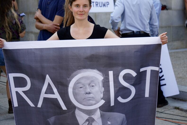 A protestor holds a sign decrying President Trump's racism at a rally in Portland, Maine on 08/04/2016