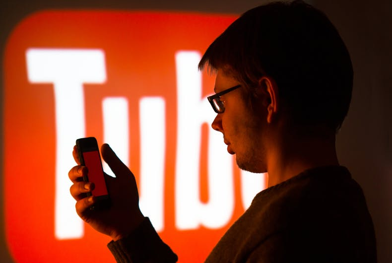 A person using their phone with the YouTube logo
