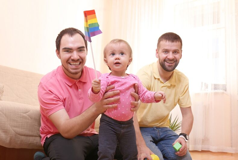 Gay couple with a baby and a rainbow flag