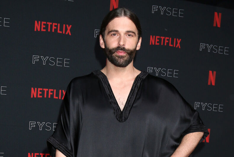 Jonathan Van Ness, a bearded white man with long hair, stands in a black shiny dress at a Netflix red carpet event.