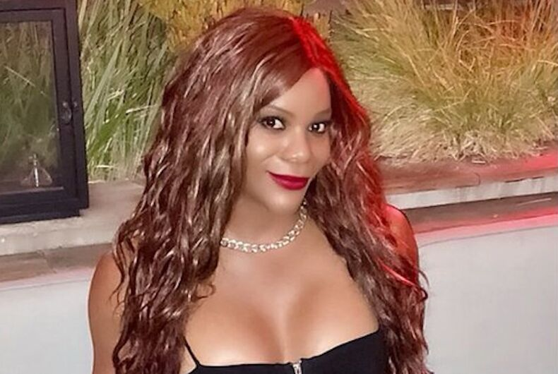 Blossom-Chrishelle Brown is a black trans woman smiling at the camera with long hair.