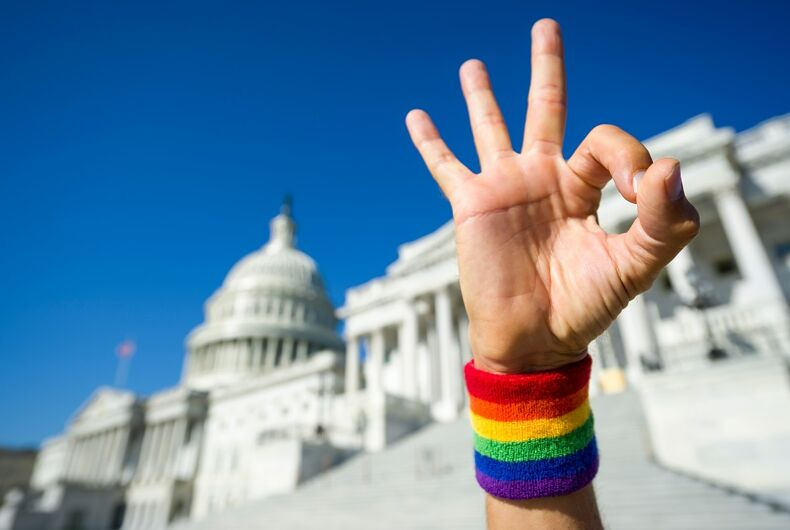 Capitol with a hand in front of it with a rainbow wrist-warmer