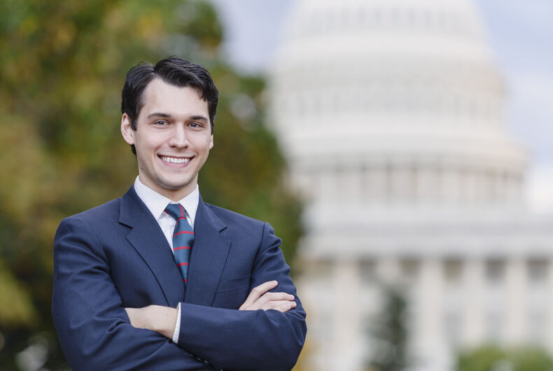 A man in a suit smiles in front of the U.S. Congress building