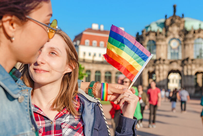 Two young women hold a rainbow flag