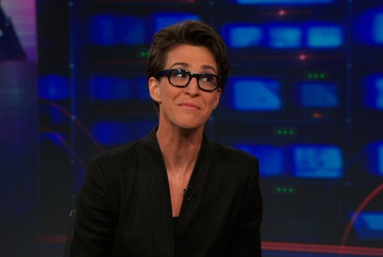 Rachel Maddow, a lesbian newscaster in horn rimmed glasses, grimaces while on
