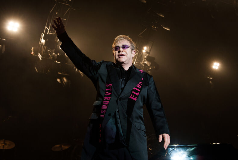 Elton John waves at a concert.