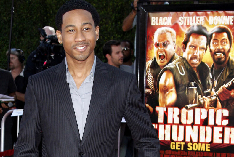Brandon T. Jackson wears a suit and stands next to a