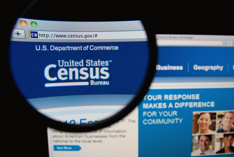 Photo of the United States Census Bureau homepage on a monitor screen through a magnifying glass.