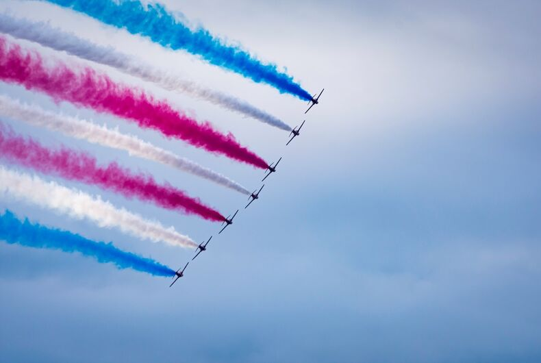 Aircraft performance and formation of 7 planes banking to form a stunning curved red blue and white smoke trail against a cloudy sky with side by side arangement