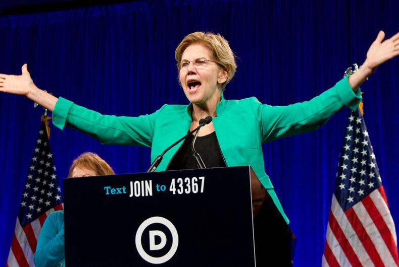 Elizabeth Warren wears a blue blazer while speaking at a lectern onstage.